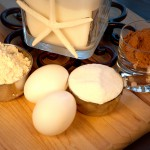 Cape Cod cooking class ingredients eggs, flour, sugar and spices on a wooden cutting board.