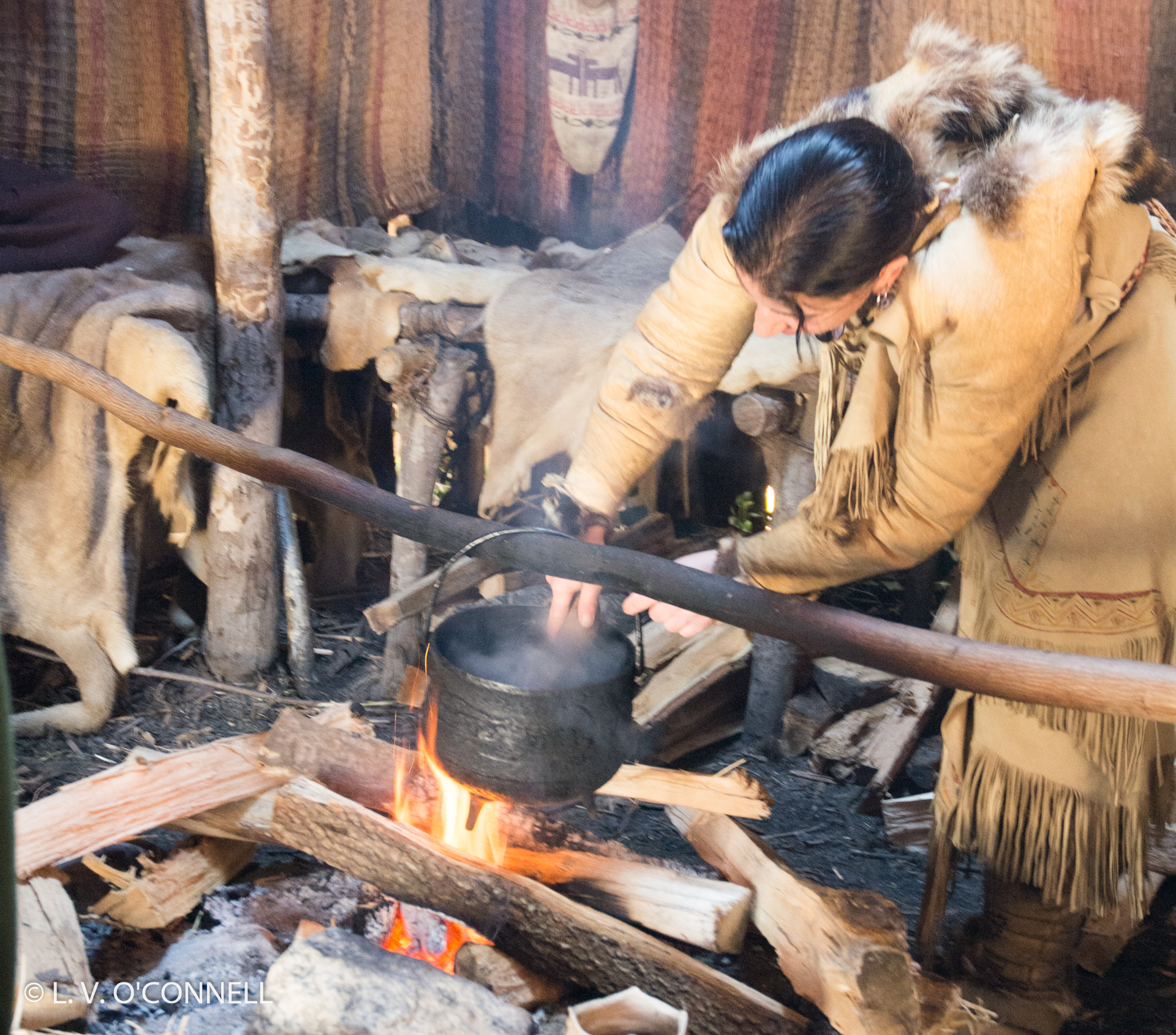 A  Wampanoag stirs stew over a fire in a Wetu.