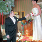 Groom helps the bride down the main stairs. Winter Wedding