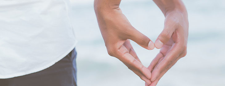 couple's hands making a heart at the beach in Cape Cod