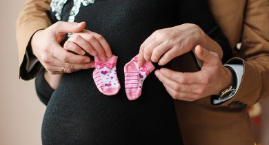 Pregnant woman and her husband holding baby socks