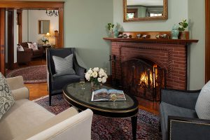 Seating area with couch, chairs, table and fireplace at our Falmouth B&B