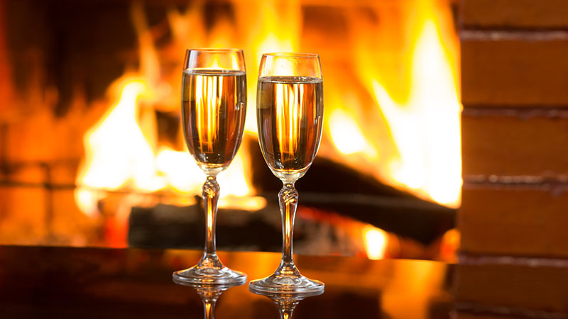 Two glasses of sparkling white wine in front of warm fireplace