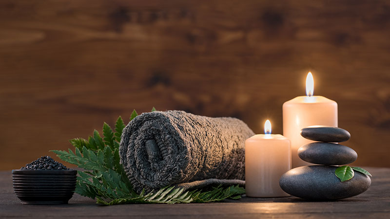 Towel on fern with candles and black hot stone on wooden background