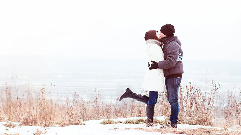 couple kissing by the coast in the winter