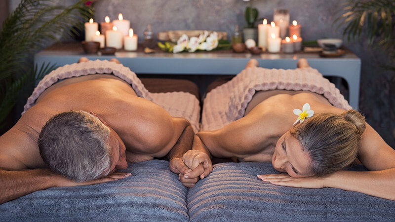 couple holding hands on massage tables