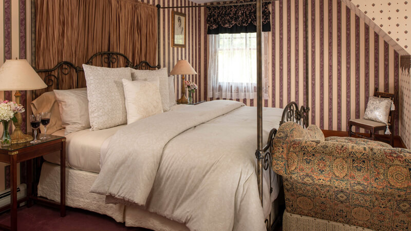 Romantic Bedroom at Palmer House Inn with brass poster bed and striped walls