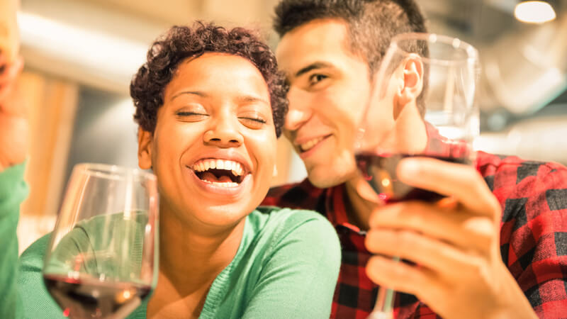 Mixed race couple laughing and holding glasses of wine