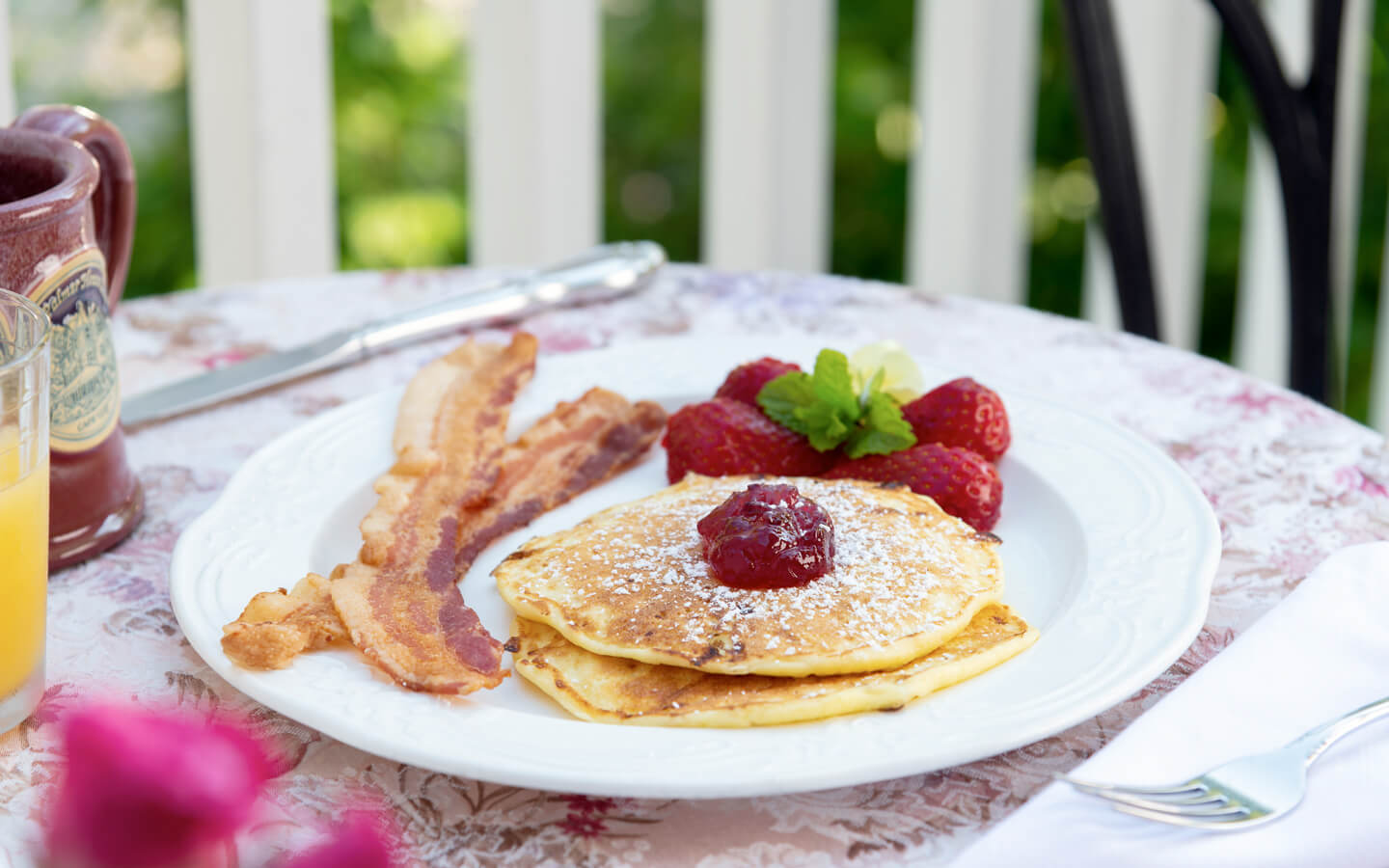 Delicious breakfast of pancakes, bacon and fruit