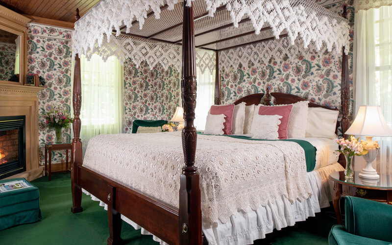 Victorian inn room with canopy bed and fireplace