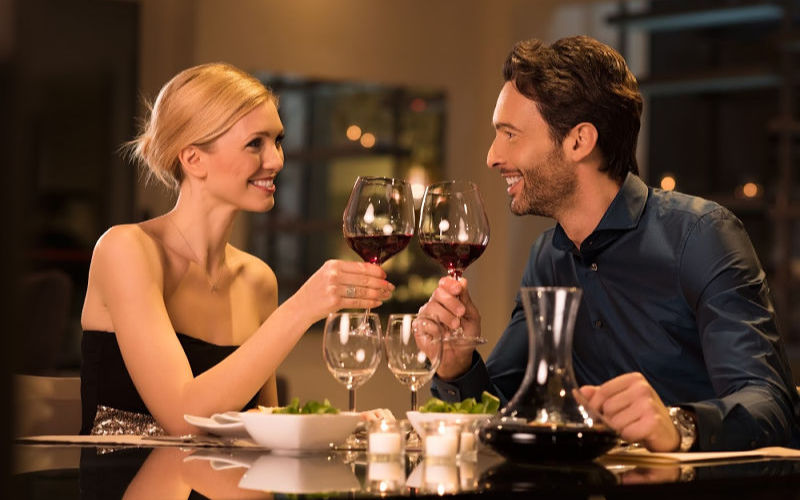 Couple in romantic restaurant with glasses of red wine
