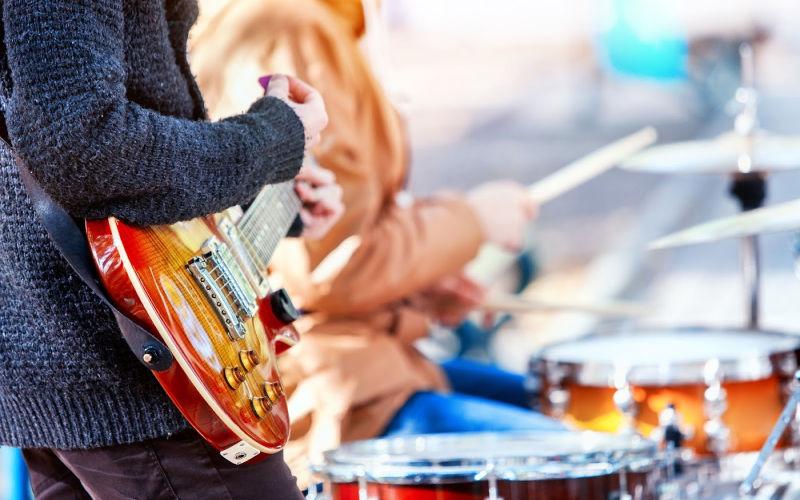 a man playing a guitar at an outdoor concert