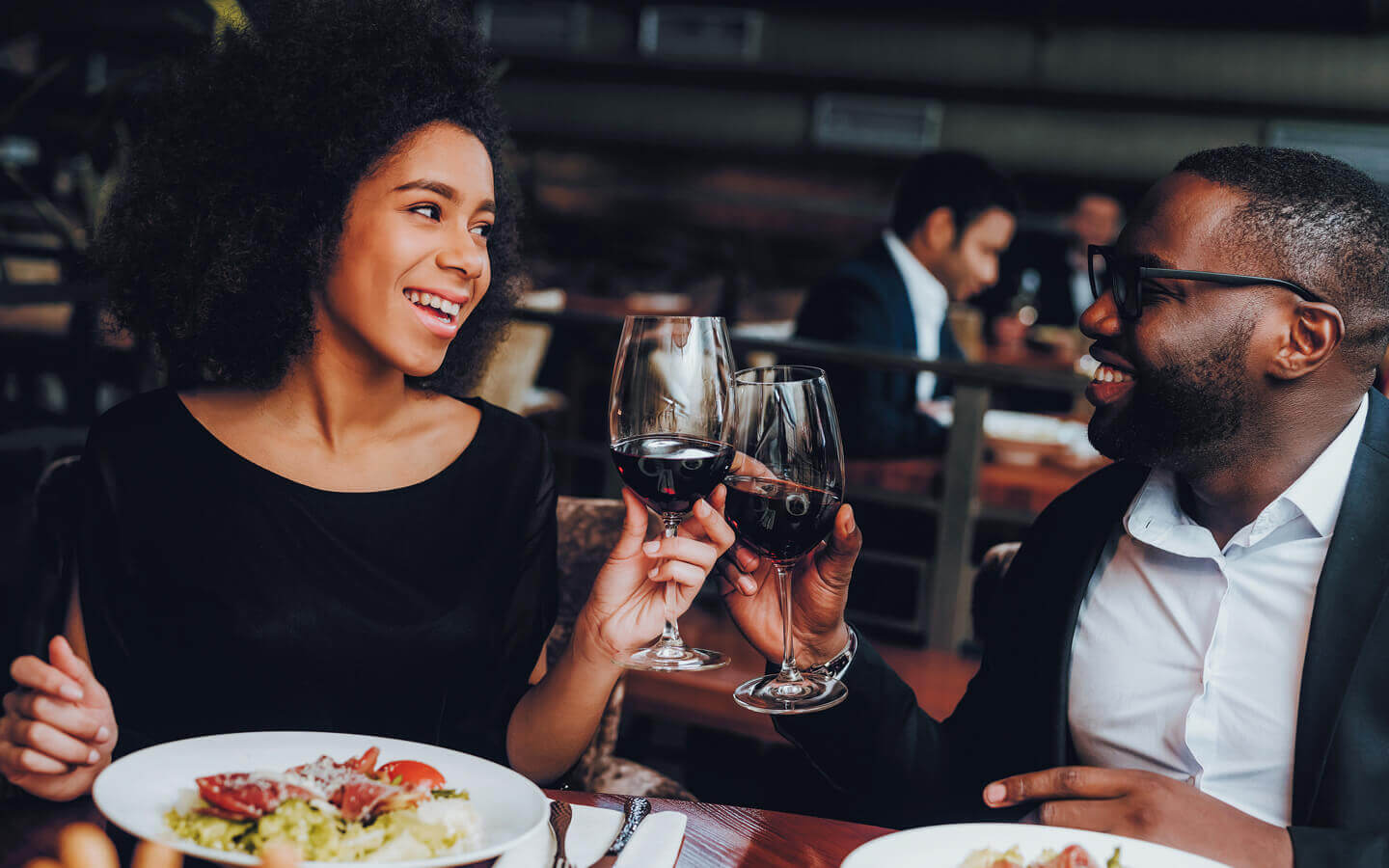African American couple enjoying dinner with red wine