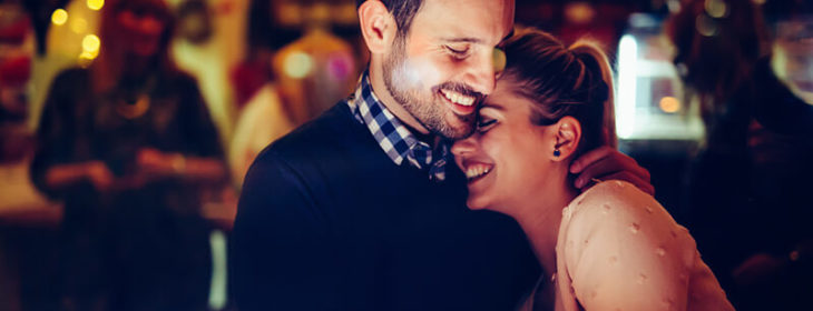 Cute happy couple embracing and smiling in a dark bar