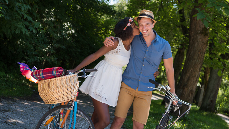 Cute interracial couple kissing next to bicycles