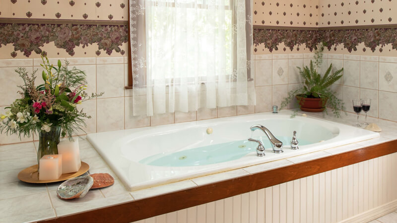 Romantic jetted tub with candles, flowers and wine