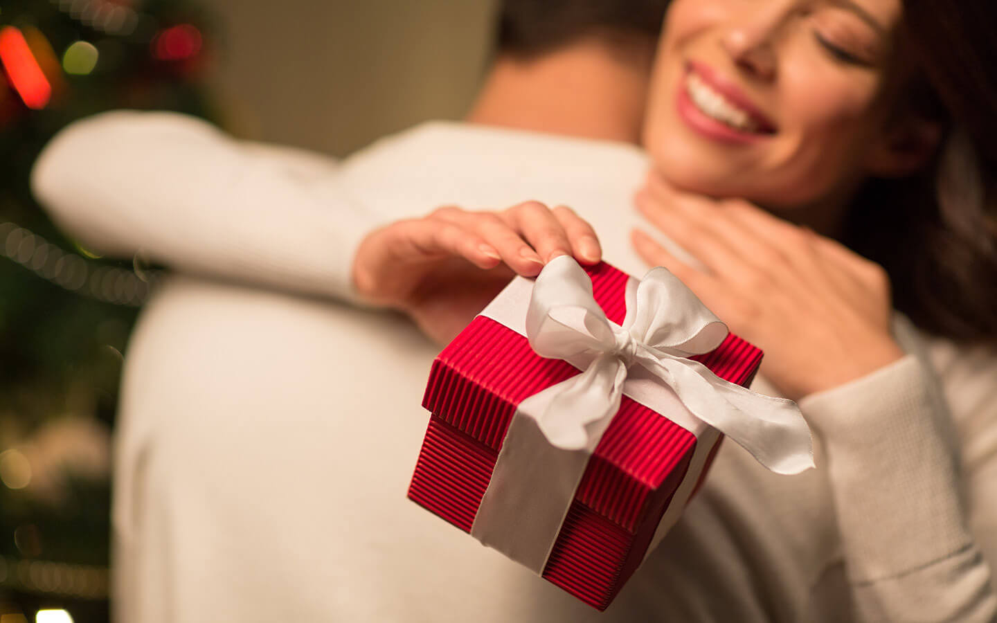 Romantic couple hugging and woman holding a gift box