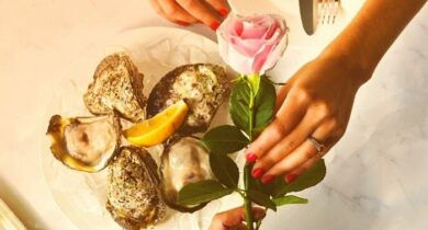 couple celebrating with oysters and rose
