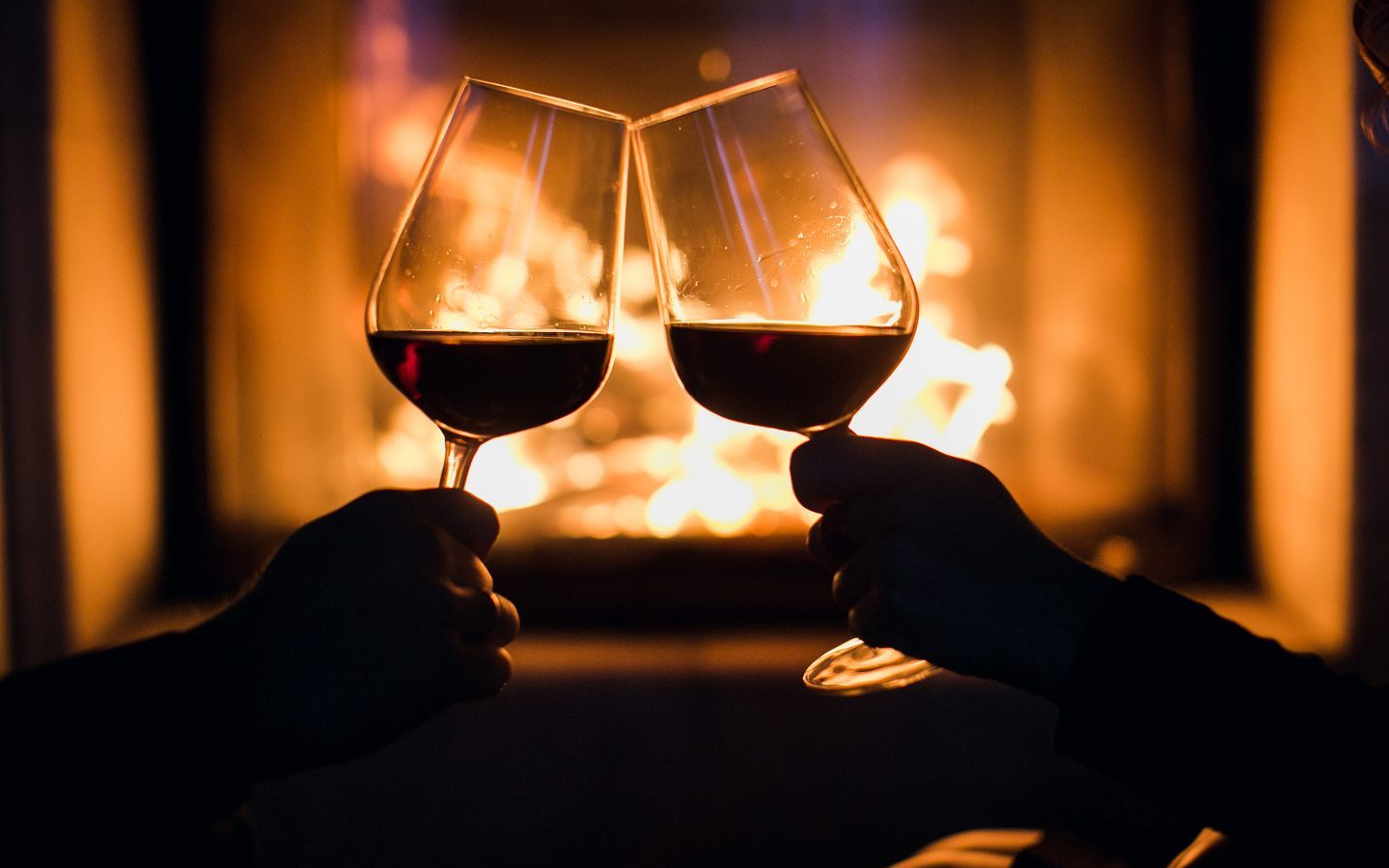 a couple toasting with two wine glasses in front of a fireplace