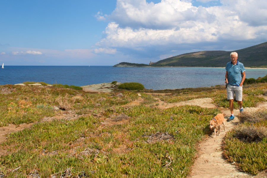a man walking a dog near the ocean